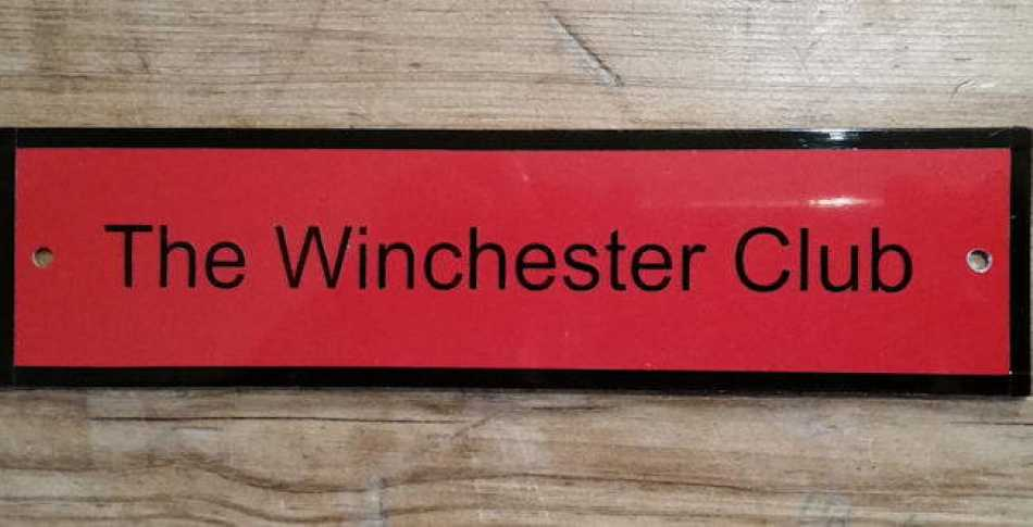 The sign on the door says that the Winchester Club is officially open.